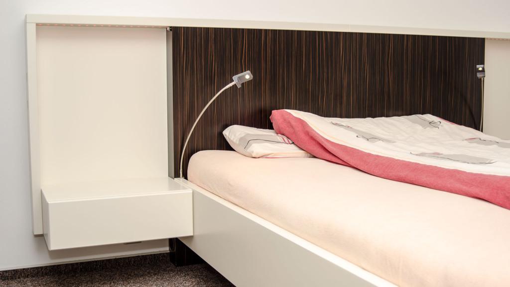 Moderní postel s RGB LED pásky v bocích nad šuplíky