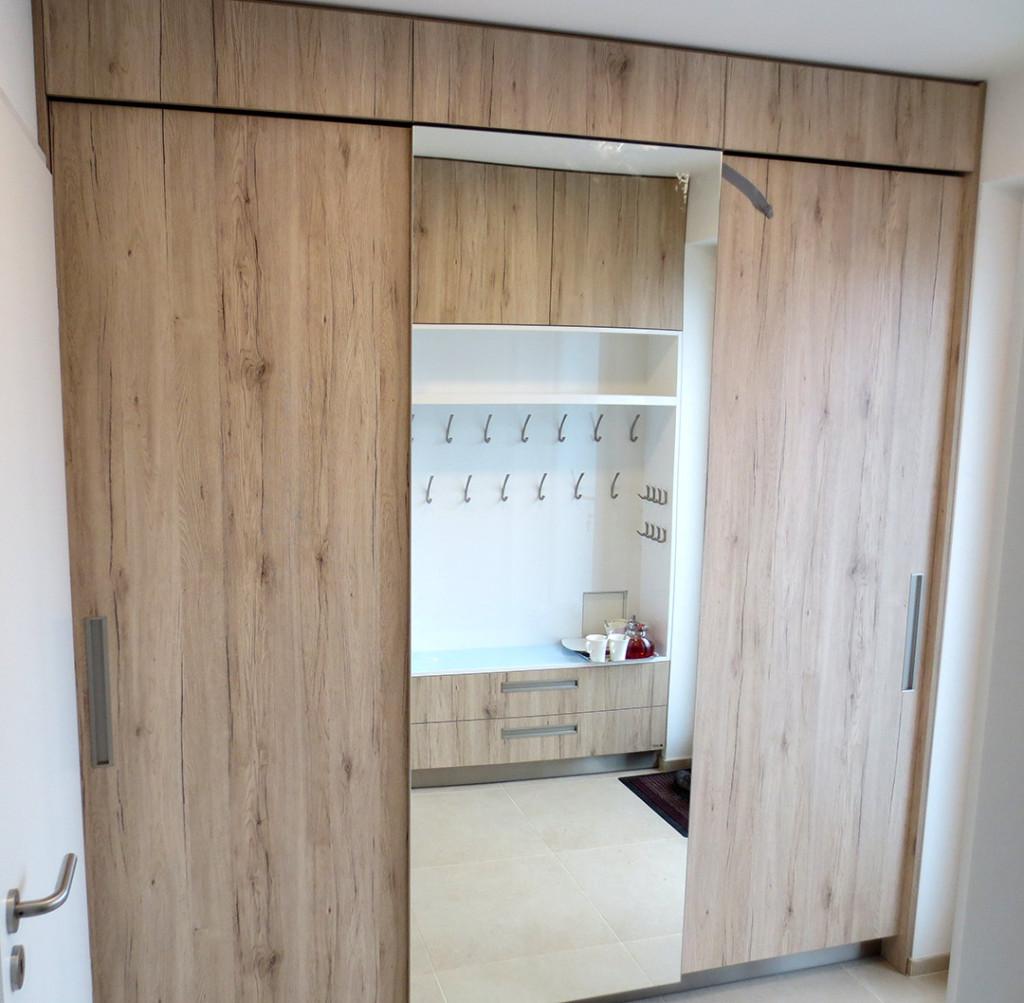 Vestavná skříň se zrcadlem, ve kterém se odráží sedák s věšáky na protější stěně