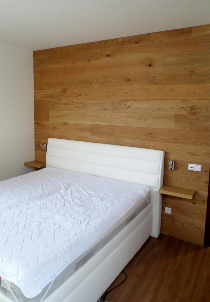 Obložení stěny za postelí s integrovanými nočními stolky