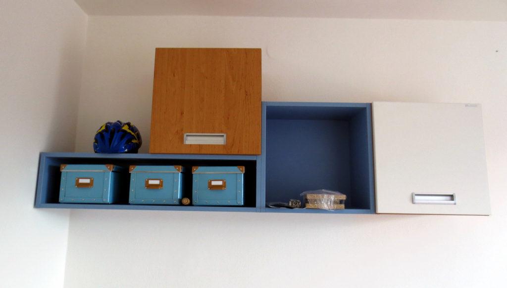 Barevné skříňky v dětském pokoji nad postelí