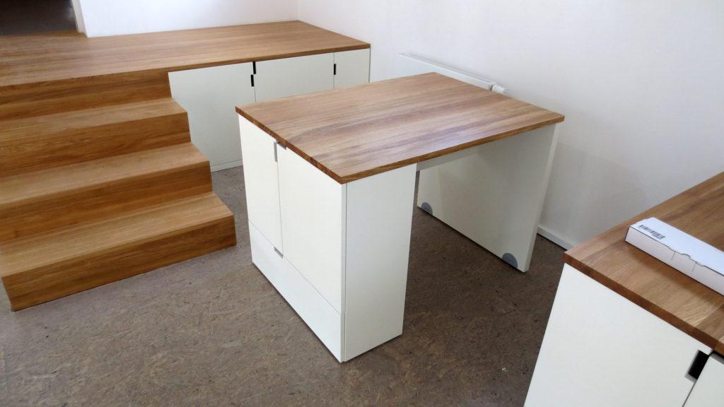 Schody s úložným prostorem a pracovní stoly na kolečkách